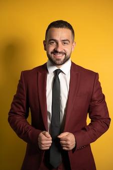 Giovane uomo bello che indossa incredibile abito bordeaux elegante che ti guarda sorridente con le mani che tengono una giacca isolata sul muro giallo