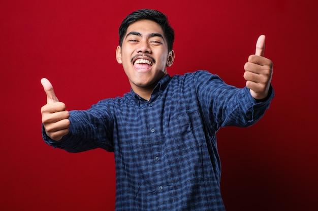 Giovane uomo bello che indossa una camicia casual su sfondo rosso che approva facendo gesto positivo con la mano, pollice in alto sorridente e felice per il successo. gesto vincitore.