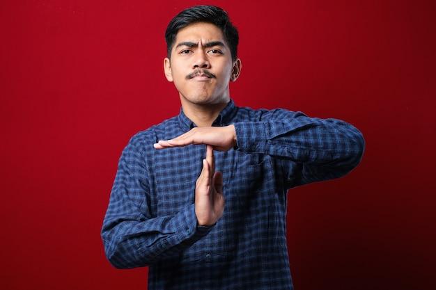 Giovane uomo bello che indossa una camicia casual in piedi su sfondo rosso facendo un gesto di time out con le mani, faccia frustrata e seria