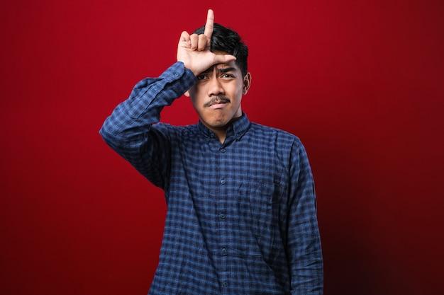 Giovane bell'uomo che indossa una camicia casual in piedi su sfondo rosso isolato che prende in giro le persone con le dita sulla fronte facendo gesto perdente che beffa e insulta.