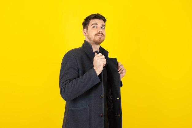 Giovane uomo bello che indossa una giacca e distoglie lo sguardo su un giallo.