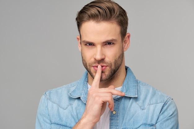 Giovane uomo bello che indossa la camicia di jeans tiene il dito sulle labbra, chiede di non dire informazioni segrete o di mantenere il silenzio