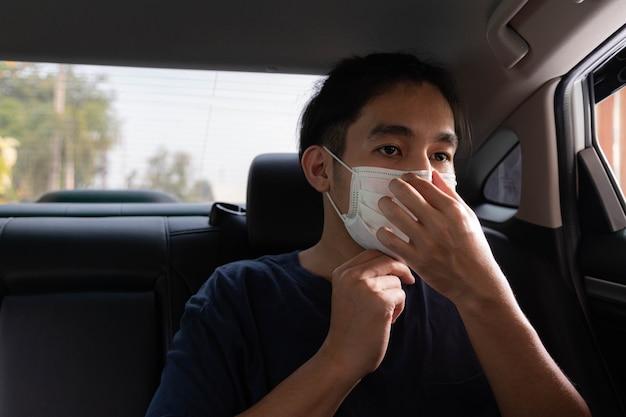 Giovane bell'uomo che indossa una maschera protettiva per proteggersi dal coronavirus mentre è seduto in macchina.