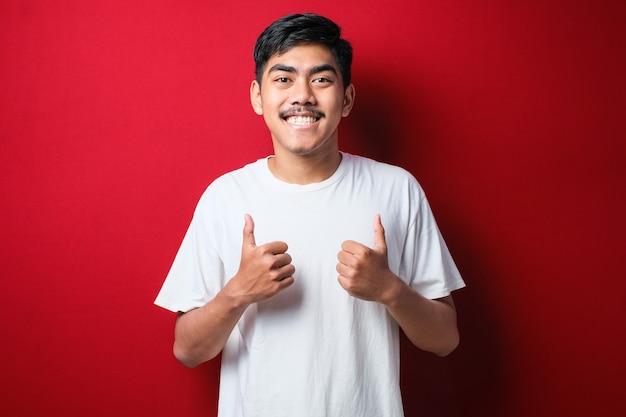 Giovane uomo bello che indossa t-shirt bianca su sfondo rosso che approva facendo gesto positivo con la mano, pollice in alto sorridente e felice per il successo. gesto vincitore.