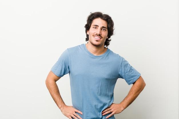 Giovane uomo bello su bianco fiducioso mantenendo le mani sui fianchi.