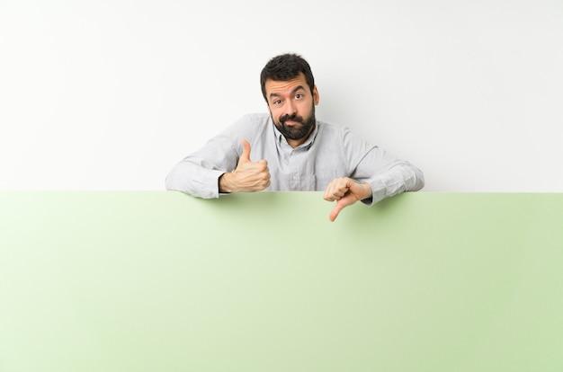 Giovane uomo bello con la barba che tiene un grande cartello vuoto verde che fa segno buono-cattivo. indeciso tra sì o no