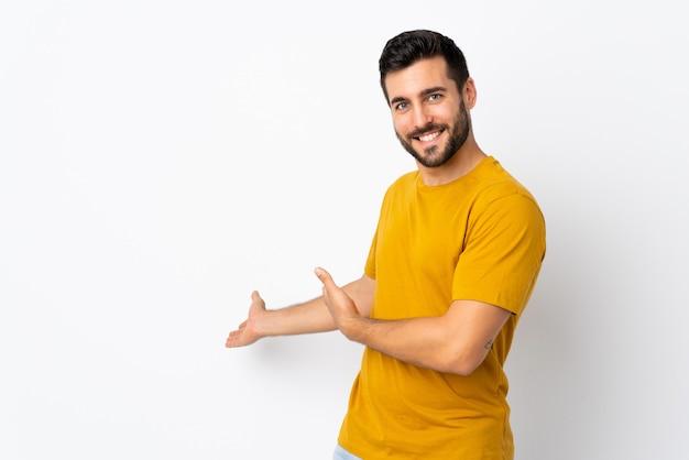 Giovane uomo bello con la barba isolata su bianco che estende le mani al lato per invitare a venire