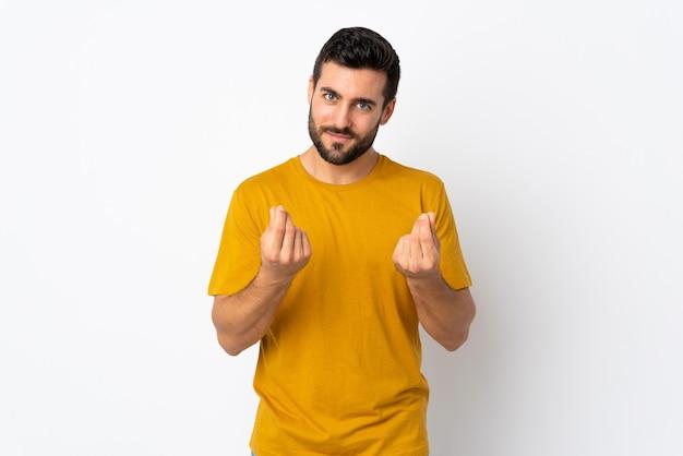 Giovane uomo bello con la barba isolata su bianco che fa il gesto dei soldi ma è rovinata