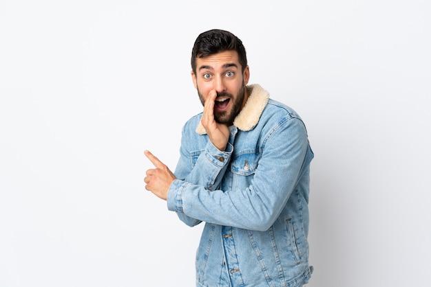 Giovane uomo bello con la barba isolato sul muro bianco che punta verso il lato per presentare un prodotto e sussurrando qualcosa