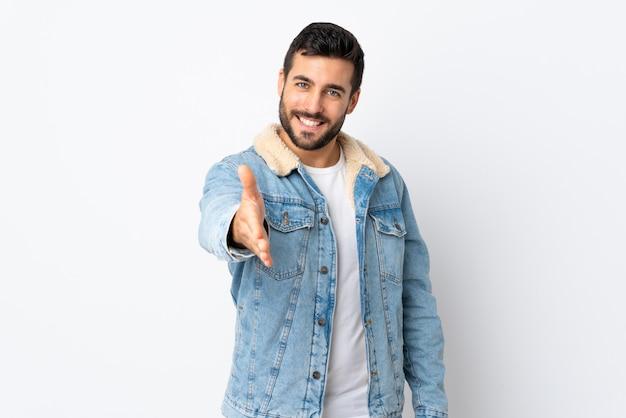 Giovane uomo bello con la barba isolata sulla parete bianca che stringe le mani per chiudere molto