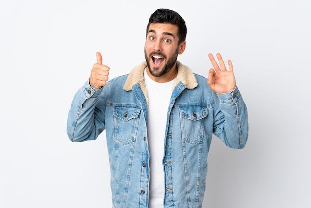 Giovane uomo bello con la barba isolata sulla parete bianca che mostra segno giusto e pollice sul gesto