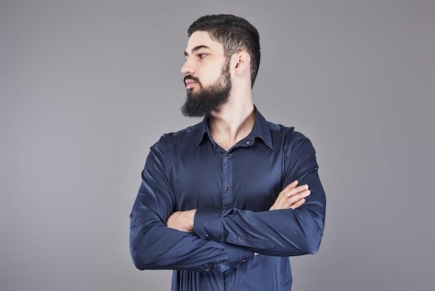 Giovane uomo bello con la barba appoggiata al muro grigio con le braccia incrociate. copia spazio.