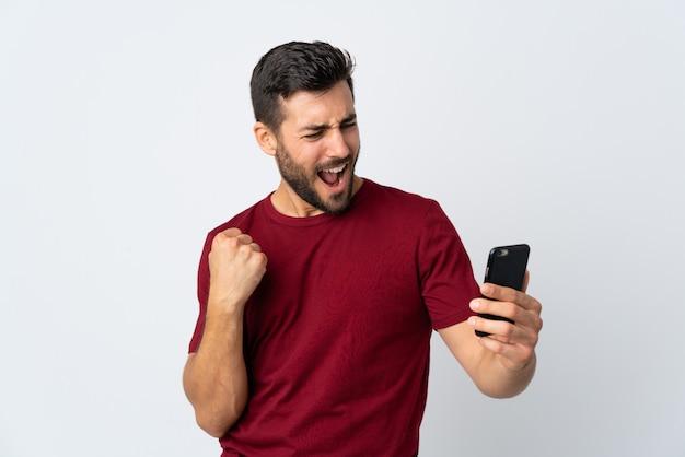 Giovane uomo bello con la barba che per mezzo del telefono cellulare isolato su bianco che celebra una vittoria