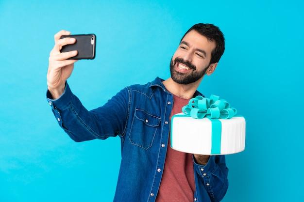 Giovane uomo bello con una grande torta sopra la parete blu isolata che fa un selfie