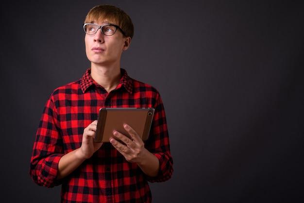 Giovane uomo bello con capelli biondi pensando e utilizzando la tavoletta digitale