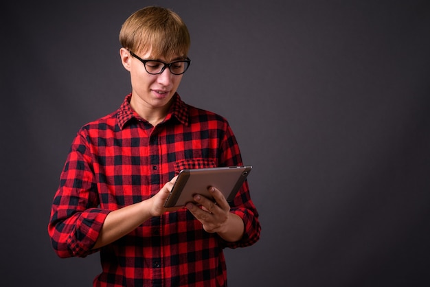 Giovane uomo bello con capelli biondi utilizzando la tavoletta digitale