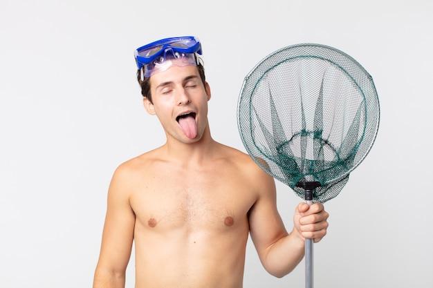 Giovane bell'uomo con un atteggiamento allegro e ribelle, scherzando e tirando fuori la lingua con gli occhiali e una rete da pesca