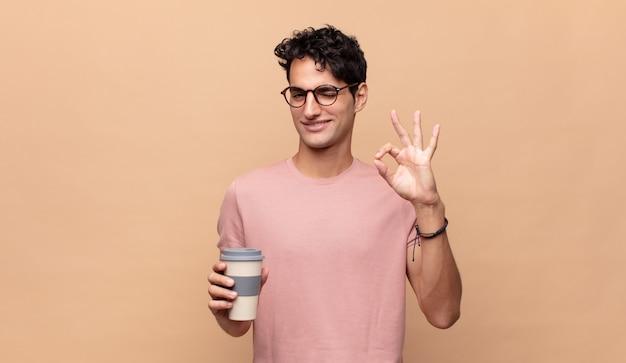 Giovane bell'uomo con un caffè che si sente felice, rilassato e soddisfatto, mostrando approvazione con un gesto ok, sorridente
