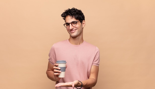 Giovane bell'uomo con un caffè che sorride allegramente, si sente felice e mostra un concetto nello spazio della copia con il palmo della mano
