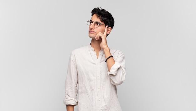Giovane uomo bello con uno sguardo concentrato, chiedendosi con un'espressione dubbiosa, guardando in alto e di lato