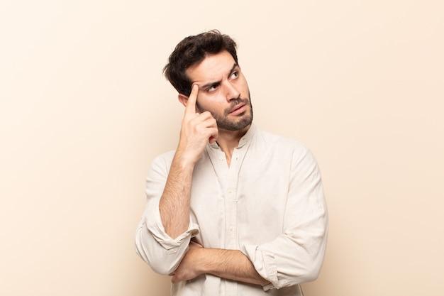 Giovane uomo bello con uno sguardo concentrato, chiedendosi con un'espressione dubbiosa