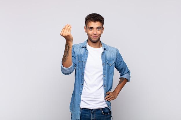 Giovane bell'uomo con camicia di jeans in posa sul muro bianco