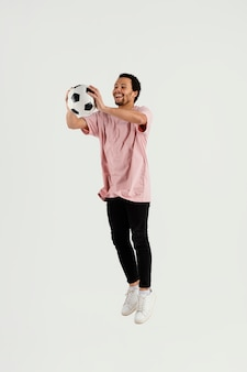 Giovane uomo bello con il salto della palla di calcio