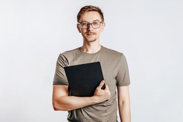 Giovane uomo bello con gli occhiali che tengono cartella per documenti con documenti su uno spazio isolato