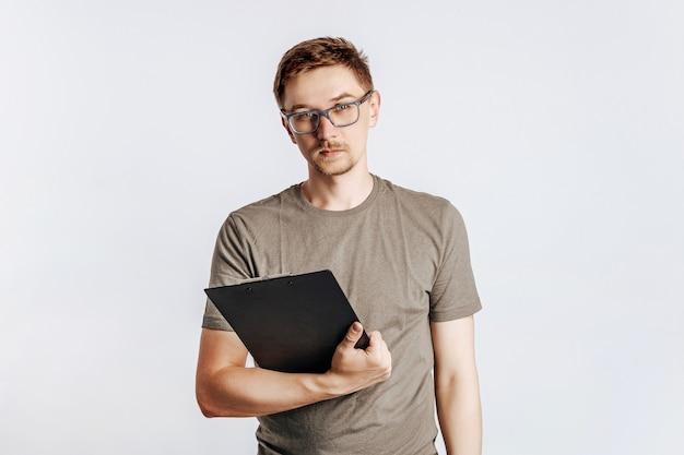 Giovane uomo bello con gli occhiali che tiene la cartella per documenti con documenti, studente, lavoratore guarda le informazioni sui dati, in posa per una foto isolata su uno spazio grigio