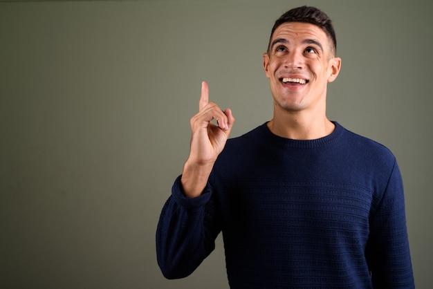 Giovane uomo bello con l'idea che punta il dito contro sfondo colorato