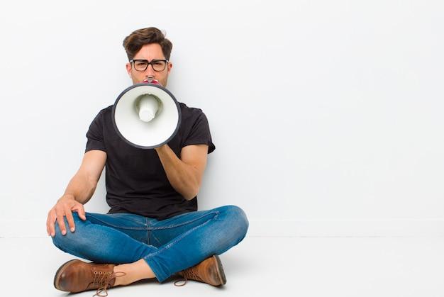 Giovane uomo bello con un megafono che si siede sul pavimento che si siede sul pavimento in una stanza bianca