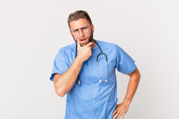 Giovane bell'uomo con la bocca e gli occhi spalancati e la mano sul mento. concetto di infermiera