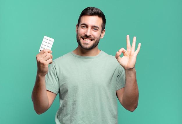 Giovane uomo bello con una tavoletta di pillole. concetto di malattia o dolore