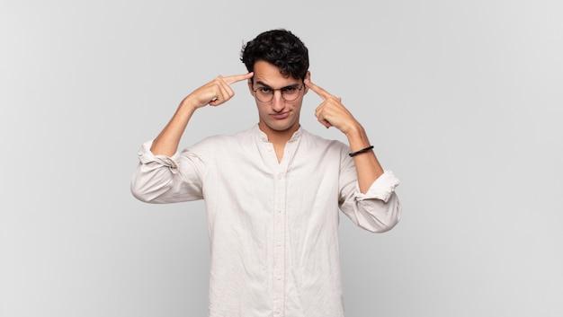 Giovane uomo bello con uno sguardo serio e concentrato, brainstorming e pensando a un problema impegnativo