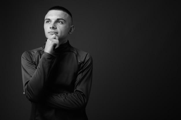 Giovane uomo bello con i capelli corti che indossa la camicia a collo alto contro il muro grigio. bianco e nero