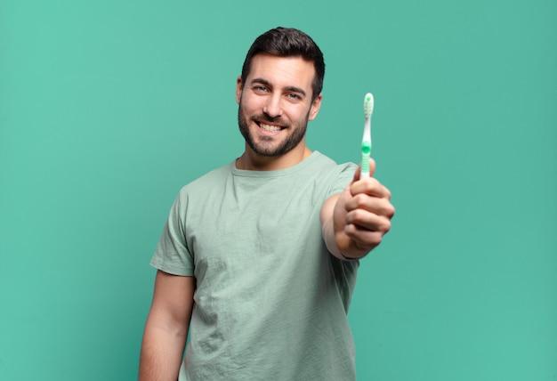 Giovane bell'uomo con uno spazzolino da denti