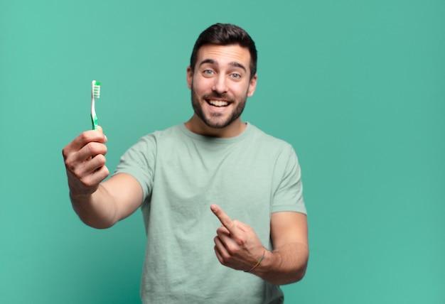 Giovane uomo bello con uno spazzolino da denti.