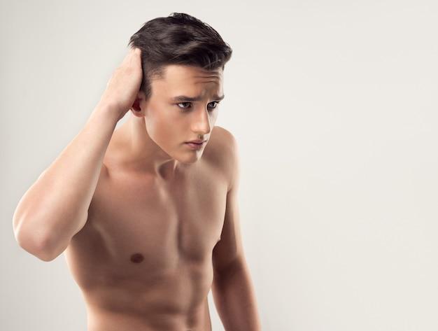 Giovane uomo bello con l'acconciatura alla moda e il torso nudo si tocca i capelli e guarda lo specchio invisibile. attrattiva dell'uomo e arte di acconciatura.