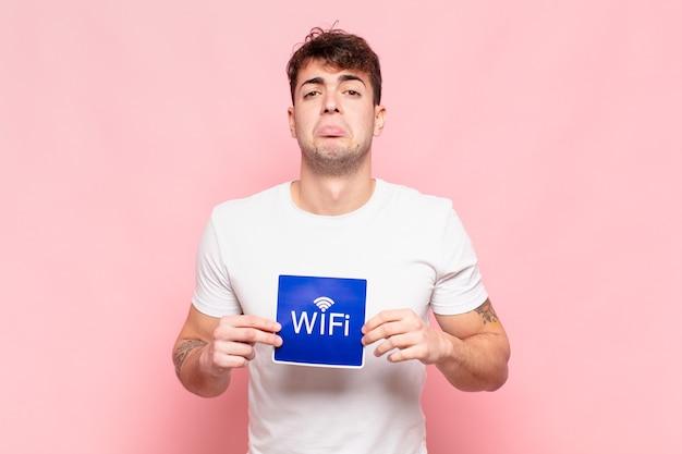 Giovane uomo bello con segno wifi