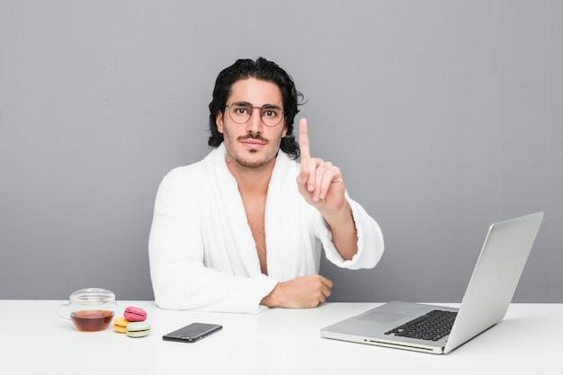 Giovane uomo bello che lavora dopo una doccia che mostra numero uno con il dito