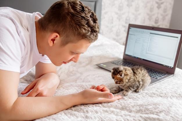 Giovane uomo bello che lavora a casa mentre mette in quarantena un coronovirus, sdraiato con un laptop e un gattino a letto