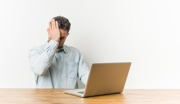 Giovane uomo bello che lavora con il suo laptop dimenticando qualcosa, schiaffeggiando la fronte con il palmo e chiudendo gli occhi.