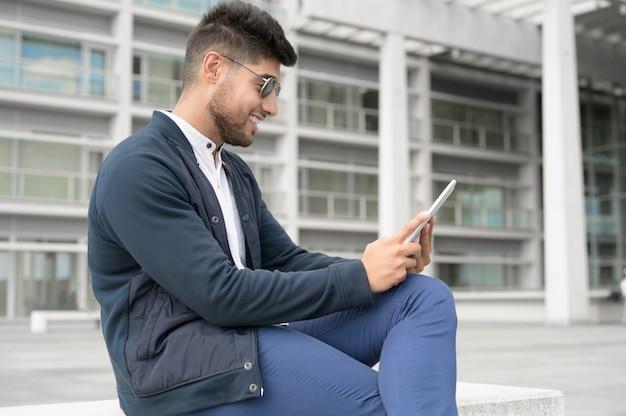 Giovani uomini belli che usano lo smartphone in città, giovane sorridente che manda un sms sul suo telefono cellulare caffè...