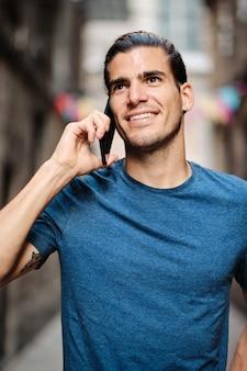 Giovane modello bello che usa smartphone e distoglie lo sguardo dalla fotocamera con una maglietta blu