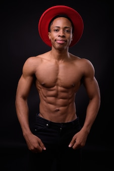 Giovane uomo africano muscoloso bello torso nudo contro lo spazio nero