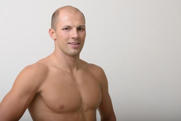 Giovane uomo calvo muscoloso bello torso nudo contro lo spazio bianco