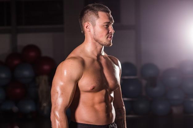 Giovane uomo muscolare bello che posa in palestra