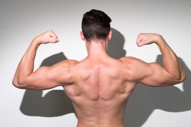 Giovane uomo muscoloso bello con capelli castani senza camicia