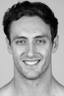 Giovane uomo muscoloso bello con capelli ondulati a torso nudo isolato in bianco e nero
