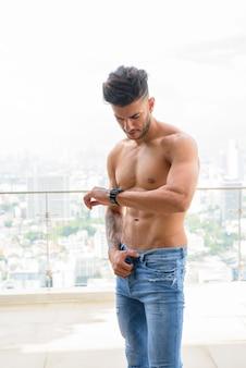 Giovane uomo persiano muscoloso bello senza camicia che controlla il tempo contro la vista della città